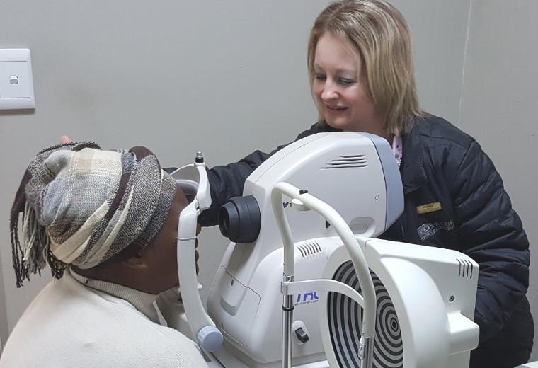 Radue optometrist using machine to test customer's eyes